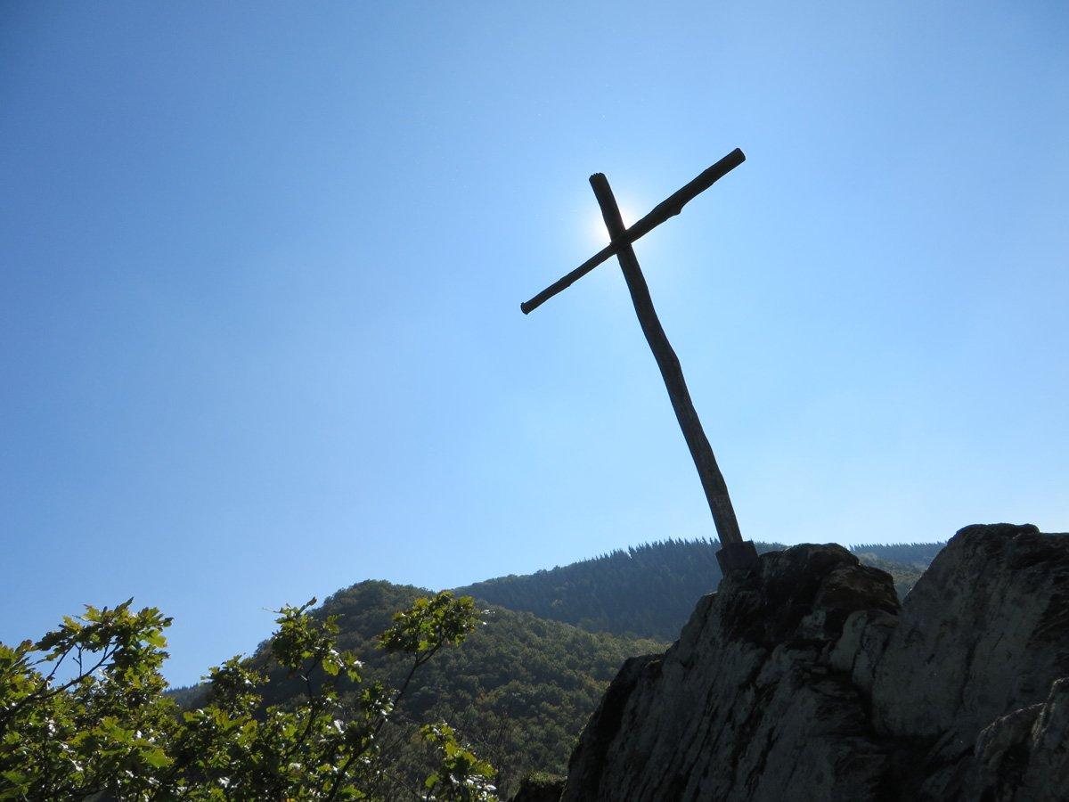 Ein karges Holzkreuz vor strahlendblauem Himmel auf einer Felsengruppe über dem Ahrtal