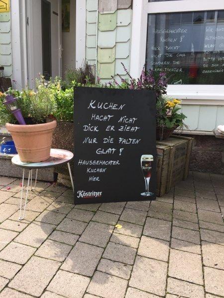 Tafel mit lustigem Spruch zum Thema Kuchen vor dem Café in Oberhof