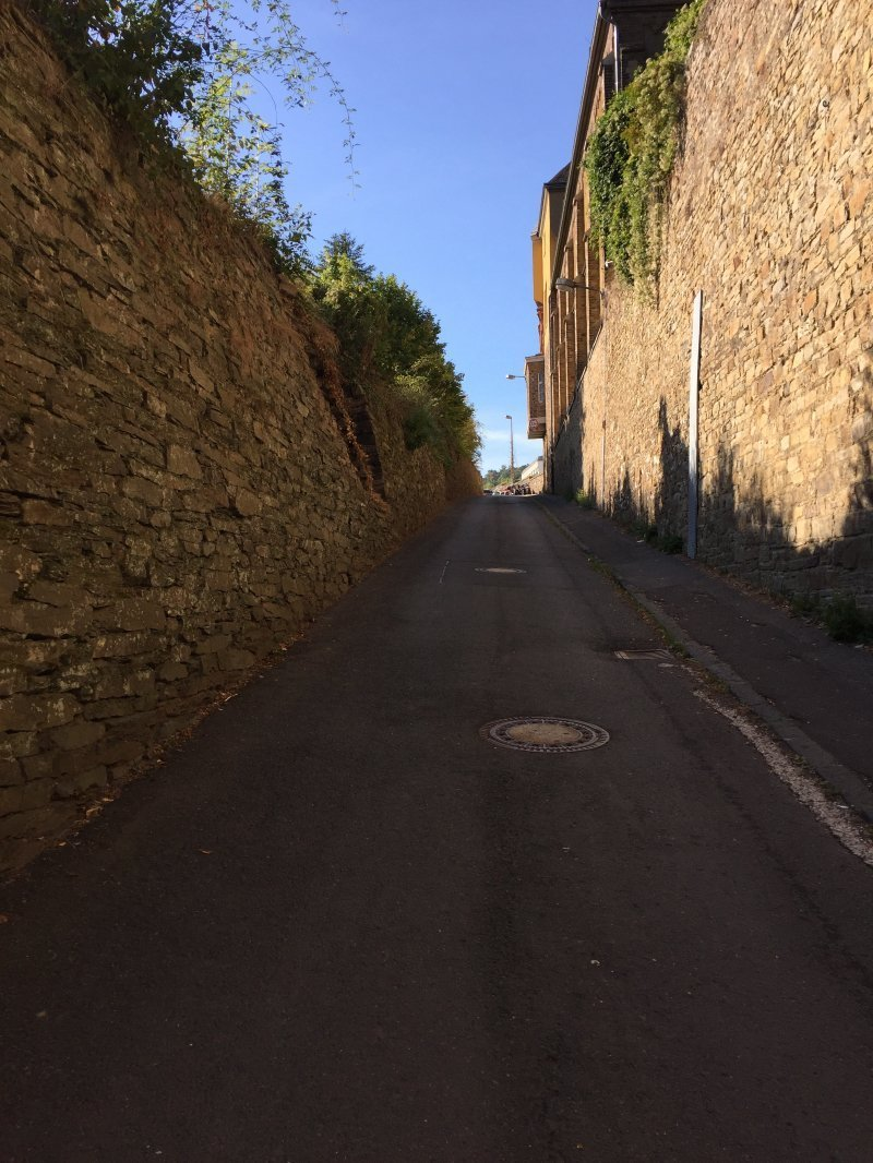 Auf dem sonnenbeschienen Weg am Kloster vorbei