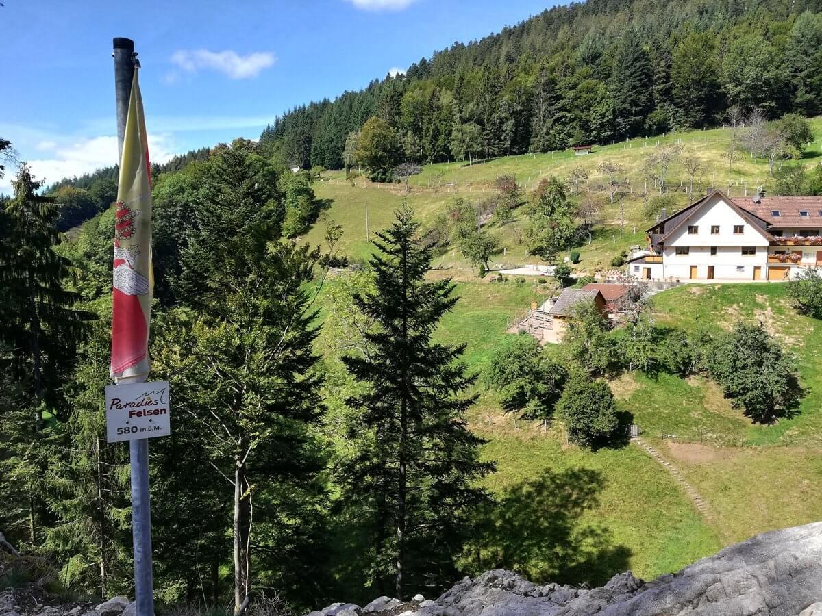 Die Fahne auf dem Paradiesfelsen, im Hintergrund ein Schwarzwaldhaus vor der grünen Silhouette eines mit Wald bestandenen Hügels