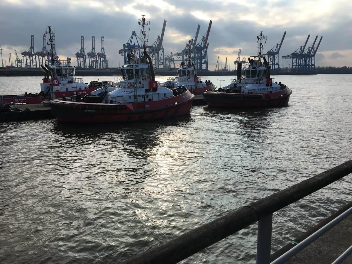 Schlepper am Kai auf der Elbe im Gegenlicht