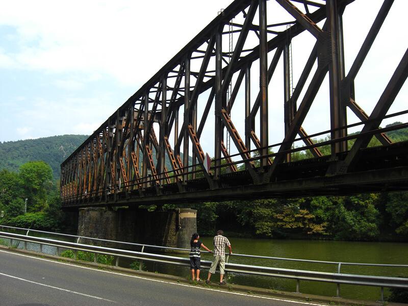 Ein rostiges Stahlfachwerk über einen Fluss, davor zwei Menschen, die sich das Wasser des Flusses anschauen